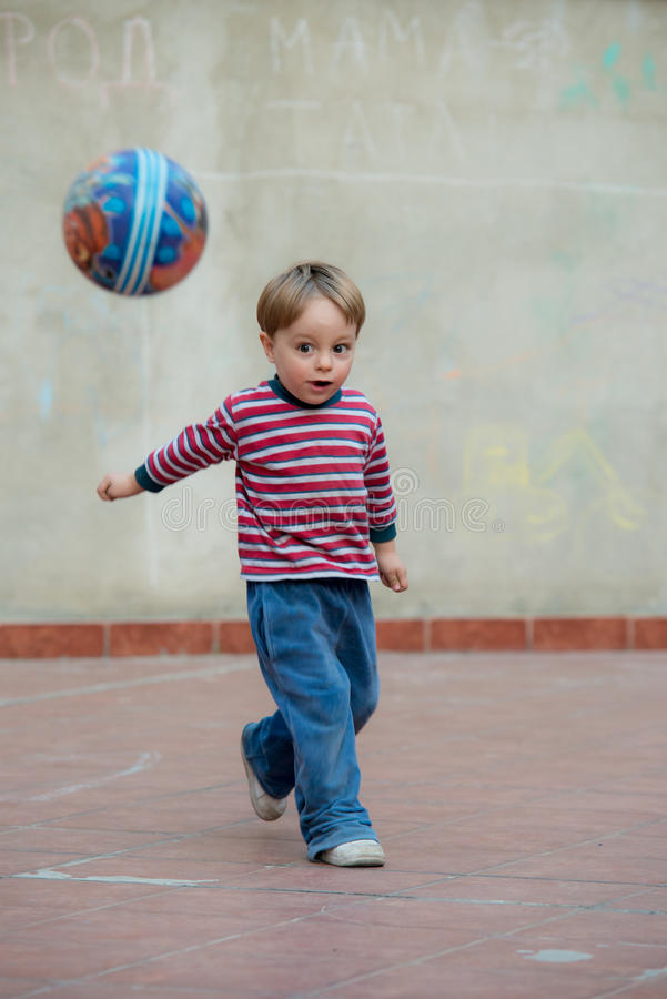 LIttle boy in the backyard with a ball. Little boy playing with a ball in the backyard royalty free stock photography