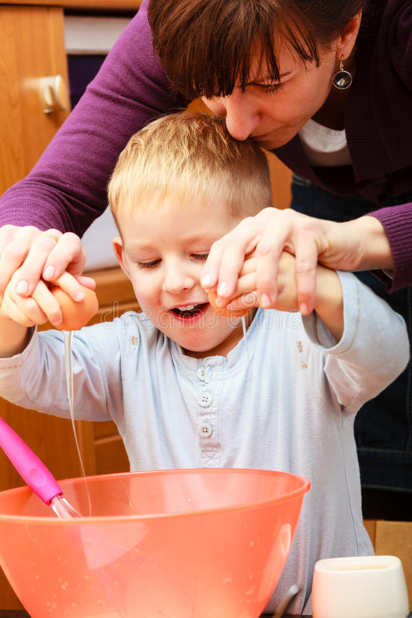 Little boy baking cake with mother, breaking egg. Happy childhood. Boy kid baking preparing cake. Mother young women teaching showing her son child how breaking royalty free stock images