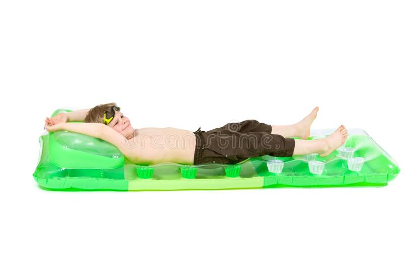 Little boy on beach mattress royalty free stock images