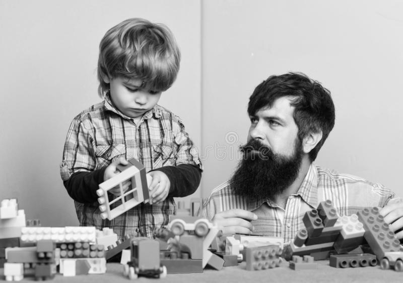 Little boy with bearded man dad playing together. child development. happy family. leisure time. building home with royalty free stock image