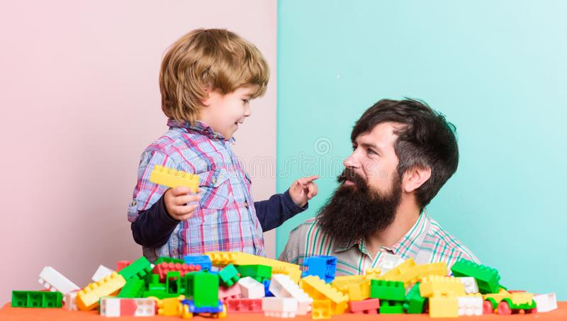 Little boy with bearded man dad playing together. happy family. leisure time. building home with colorful constructor royalty free stock photos