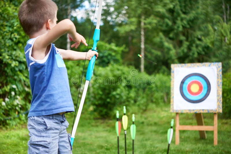 Little boy with big bow shooting in sport aim stock photo