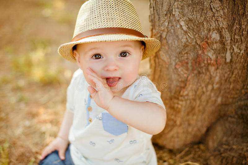 Little boy with big brown eyes and a hat sucks a finger, on the. Background of sunset in summer, close-up royalty free stock photos