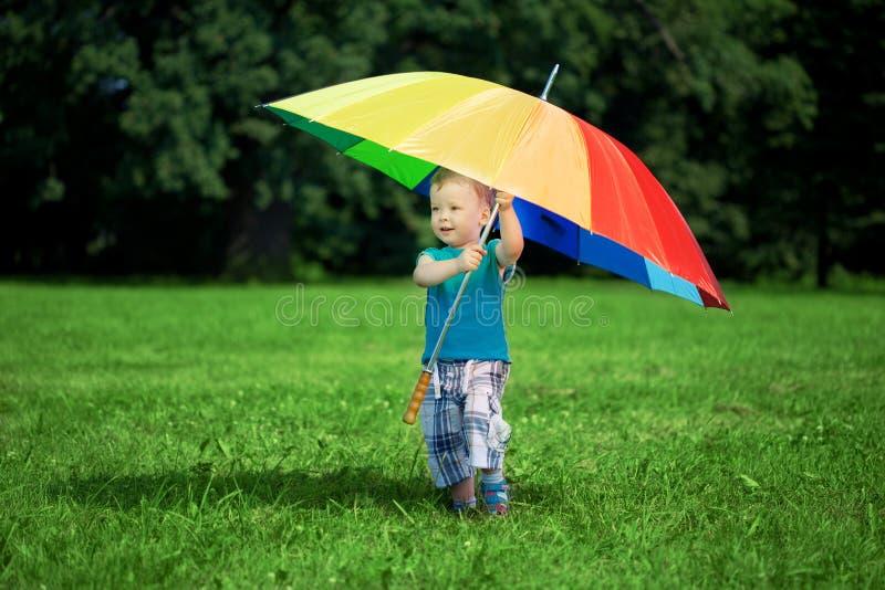 Little boy with a big rainbow umbrella stock photo