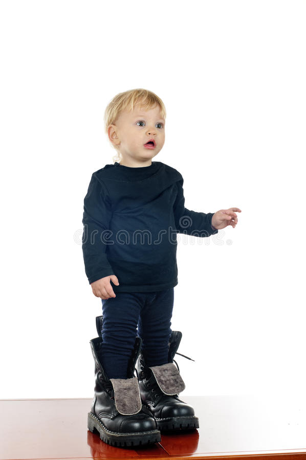 Little boy and big shoes. Two years old boy in big shoes on white stock photo