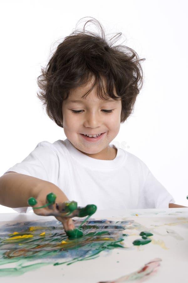 Little Boy bildet eine Fingermalerei stockbild