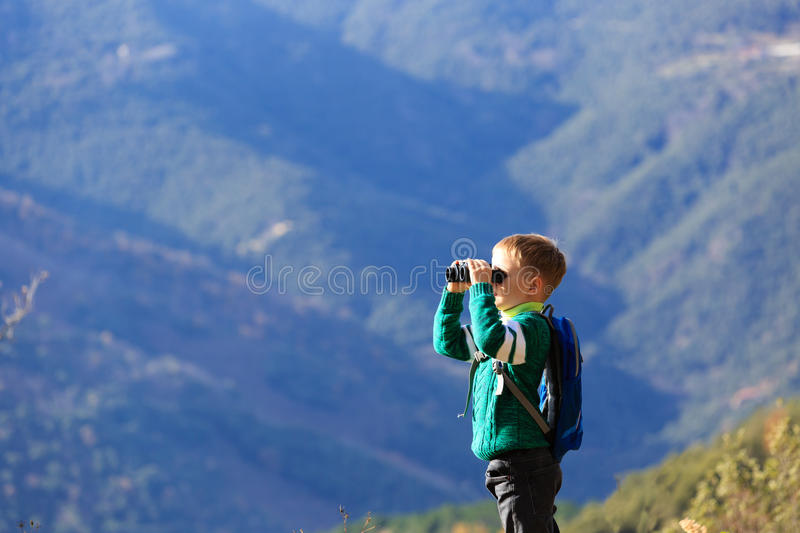 Little boy with binoculars hiking in mountains stock photography