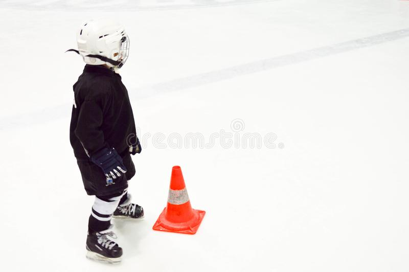 A little boy in black hockey uniform and a white helmet on skates next to an orange cone on white ice on the ice hockey royalty free stock photos