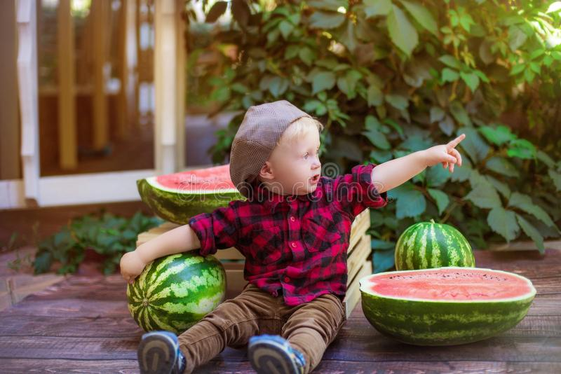 A little boy with blond hair n the summer on a sunny day sitting at a gazebo with a green grapes and eating a watermelon royalty free stock image