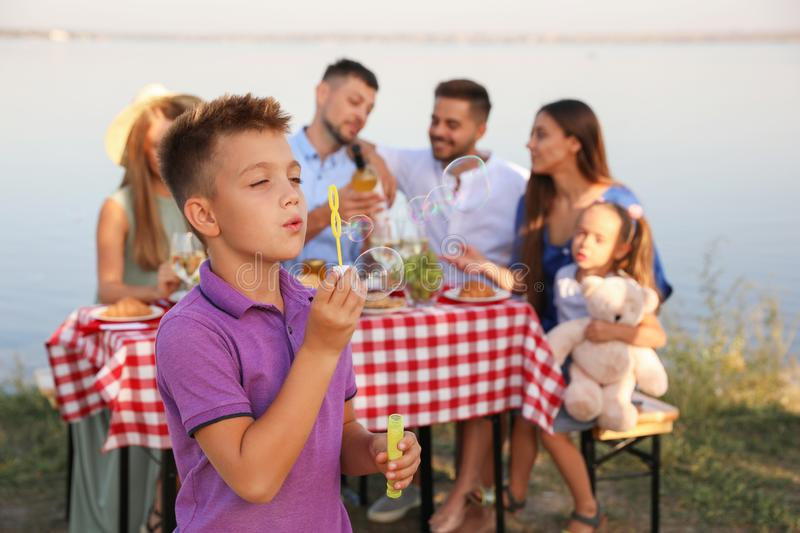 Little boy blowing  outdoors. Picnic time royalty free stock images