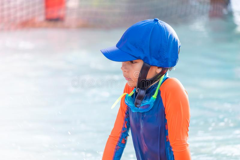 Boy with blue hat and orange suit is playing in swimming pool stock photography