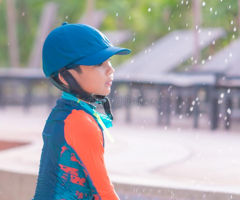 Boy with blue hat and orange suit is playing in swimming pool royalty free stock photo