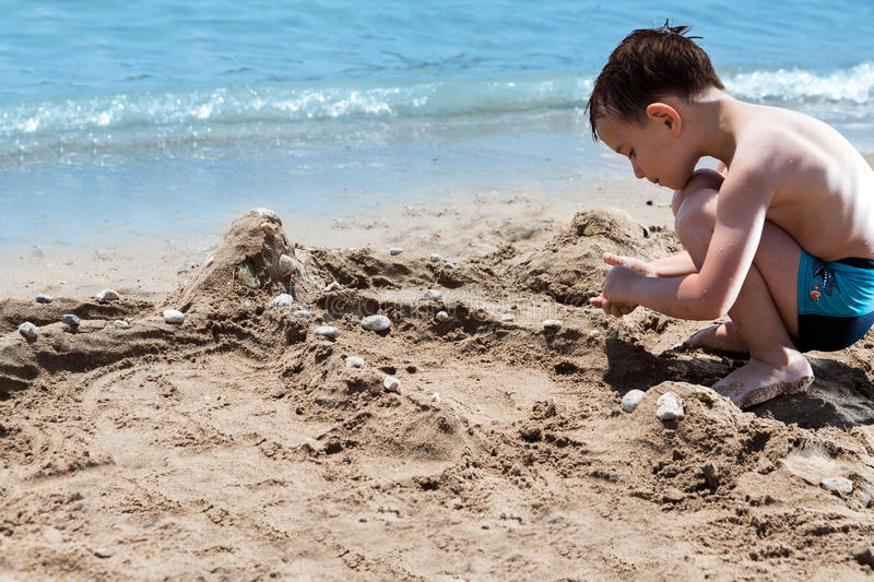 Little boy in blue sea and play with sand. Little boy in blue sea playing with mud pies and sand stock image