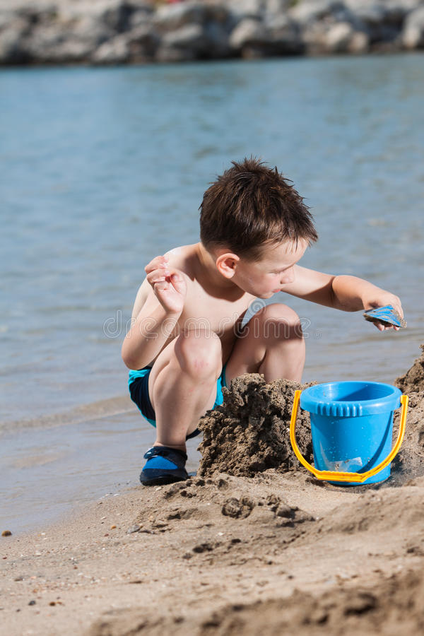 Little boy in blue sea and sand play. Little boy in blue sea playing with mud pies and sand stock image