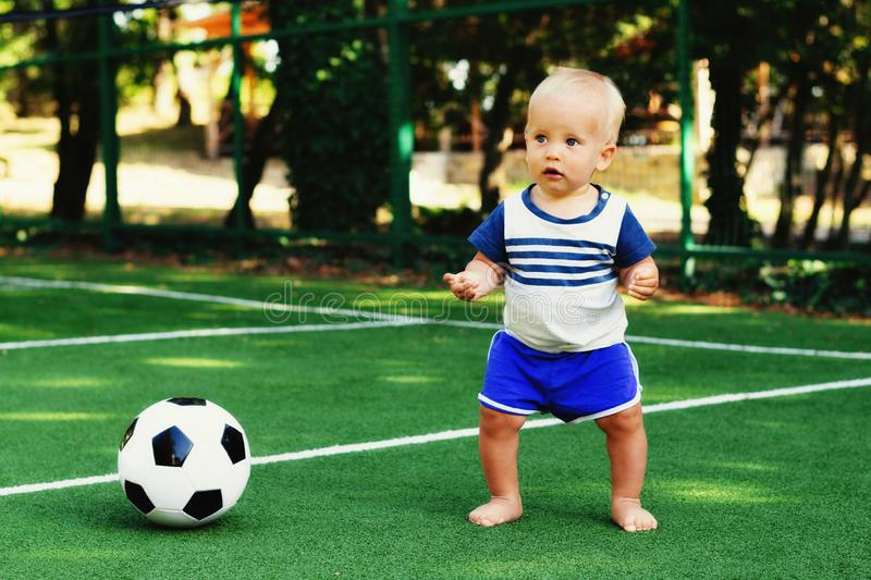 Little boy in blue shorts playing with soccer ball at sports ground. Blonde child in uniform standing at football field with ball. Little boy in blue shorts stock images