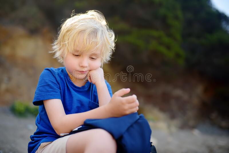 Little boy is bored during walking on nature. Sad offended child. Upset kid royalty free stock images