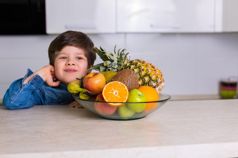 Little boy with a bowl of fresh fruits stock image