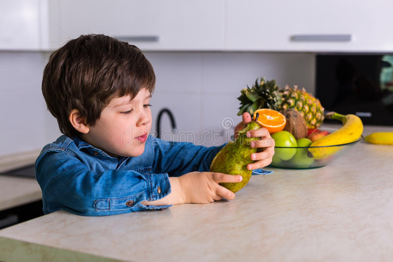 Little boy with a bowl of fresh fruits royalty free stock photo