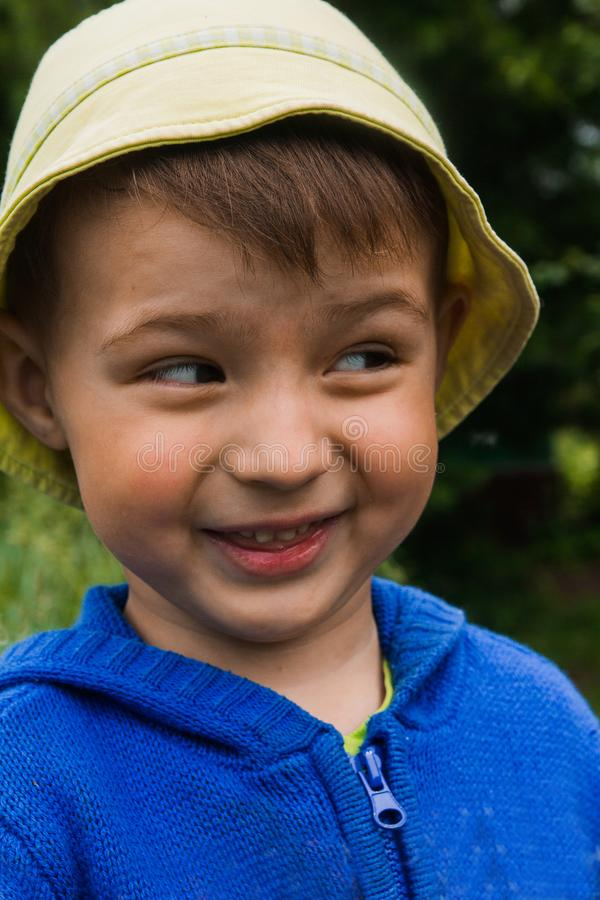 A little boy in a bright hat and blue sweater mow down his eyes and smiles royalty free stock photography