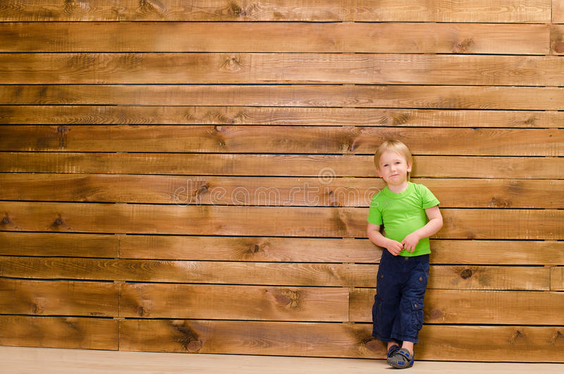 Little boy on brown wooden wall background royalty free stock photography