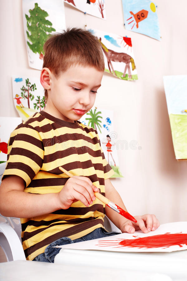 Download Little Boy  With Brush Draw Red Sun In Play Room. Stock Image - Image: 13782863