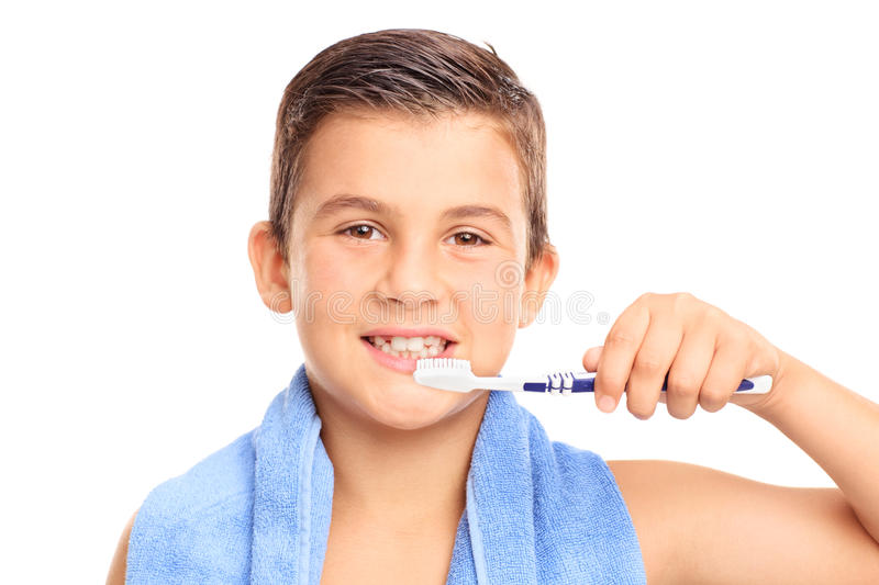 Little boy brushing his teeth with a toothbrush. And looking at the camera isolated on white background stock photo