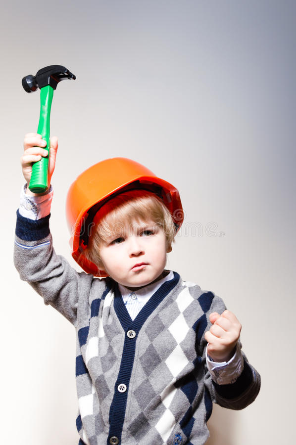 Little boy in builder helmet holding toy hammer stock photography