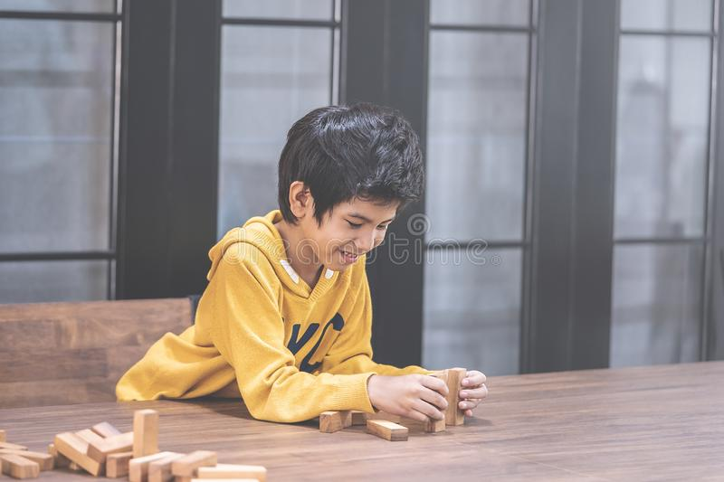 Little Boy building wooden toy block tower royalty free stock photography
