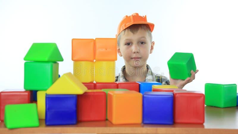 Little boy builds a house of children's blocks stock photos