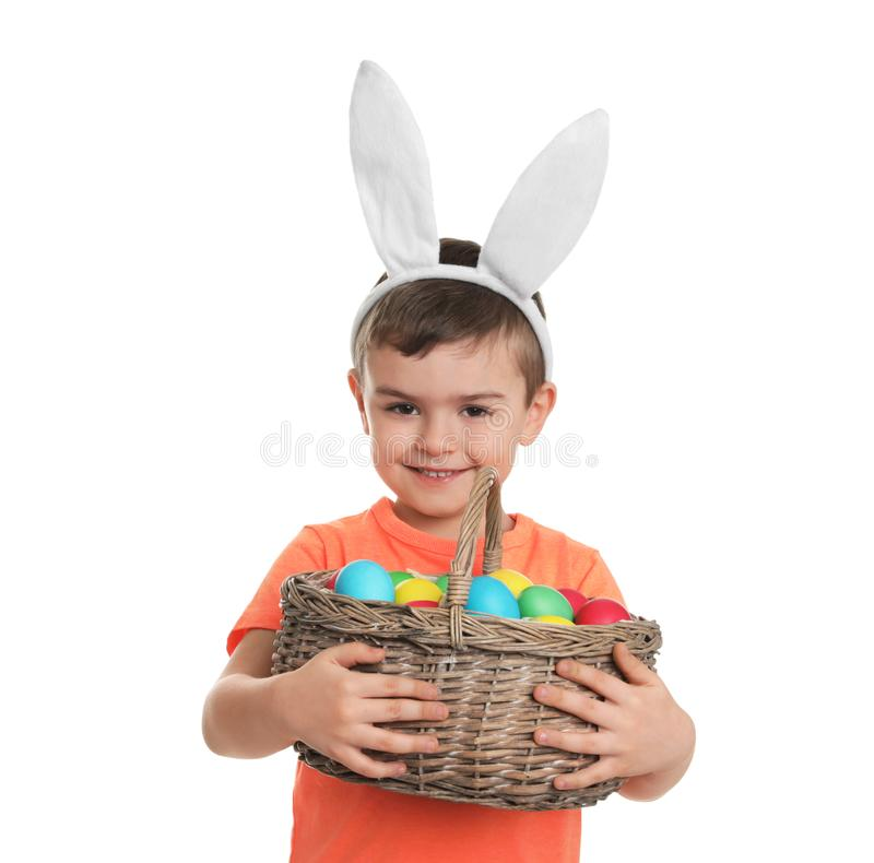 Little boy in bunny ears headband holding basket with Easter eggs on white. Background royalty free stock image
