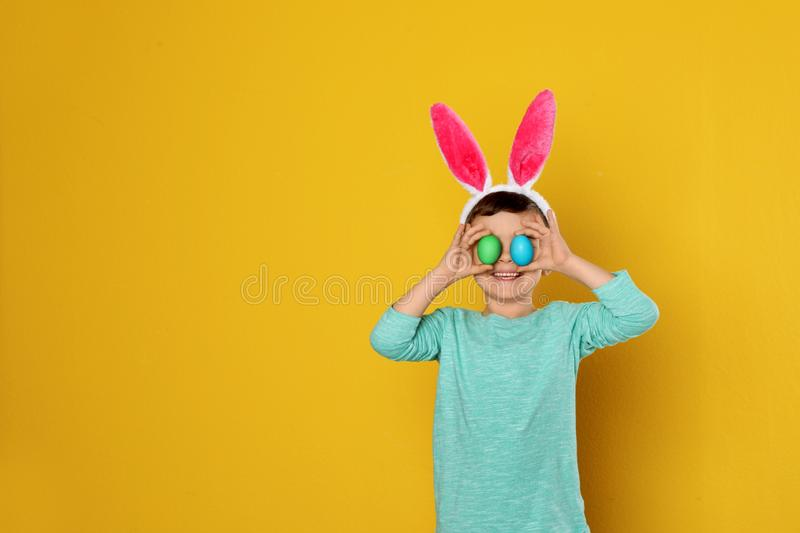 Little boy in bunny ears headband holding Easter eggs near eyes on color background. Space for text royalty free stock images