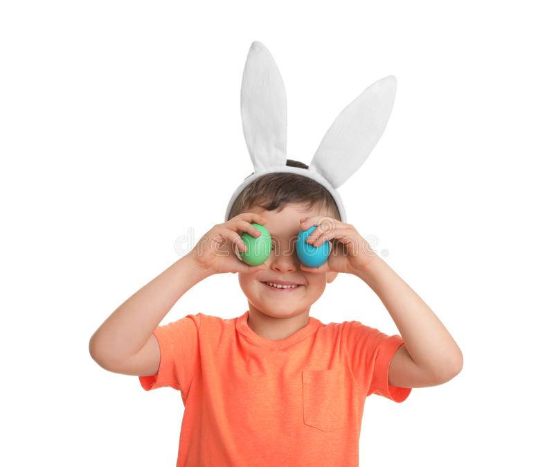 Little boy in bunny ears headband holding Easter eggs near eyes on white. Background royalty free stock images