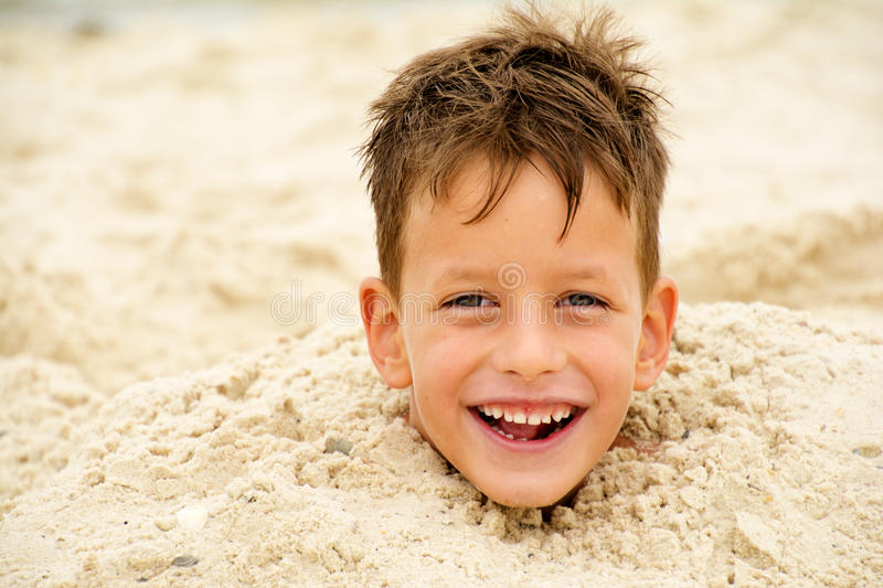 Little boy buried in the sand on beach stock photo