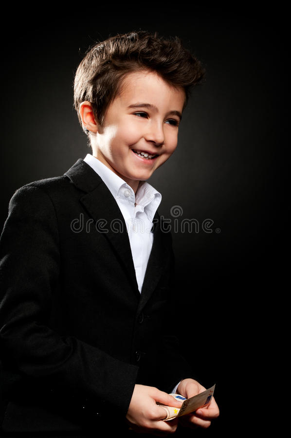 Little boy businessman portrait in low key counting money royalty free stock photos