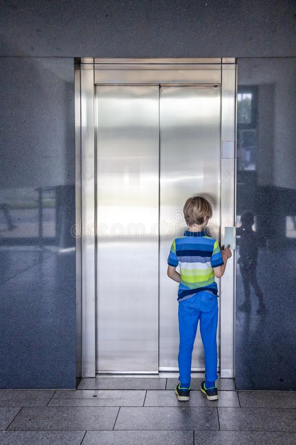 Little boy is calling the elevator royalty free stock photography