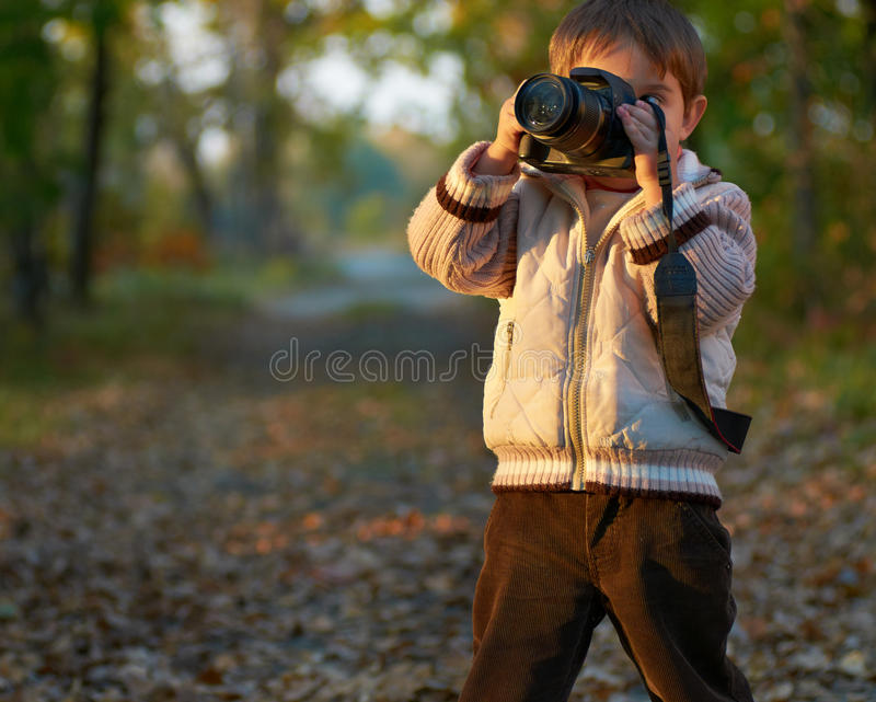 Little boy with camera in the park royalty free stock photography