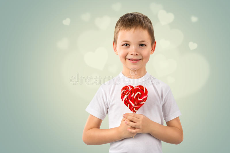 Little boy with candy red lollipop in heart shape. Valentine`s day art portrait. Cute child little boy with candy red lollipop in heart shape. Beautiful kid eat stock images