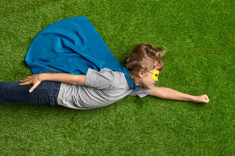 Little superhero flying over grass. Little boy in cape and mask lying in flying pose on green lawn while pretending to be superhero stock photography