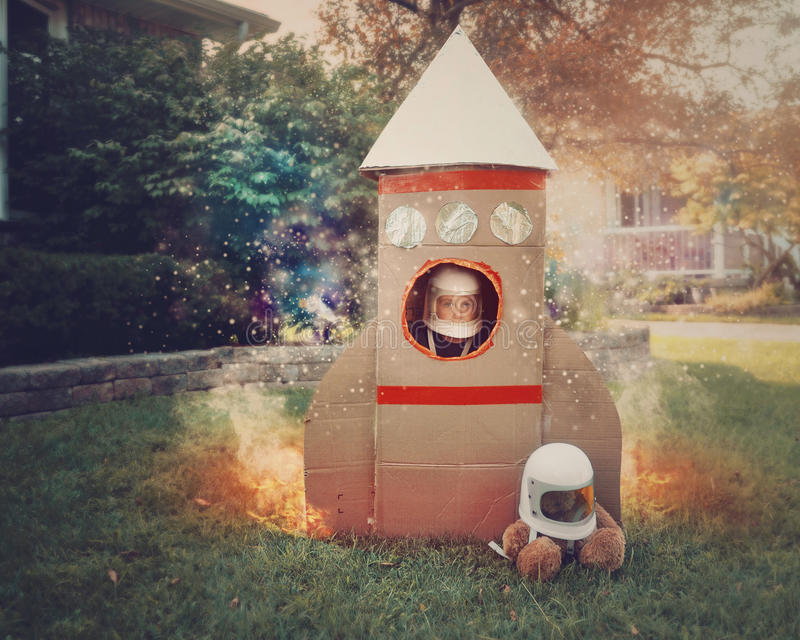 Little Boy in Cardboard Rocket Ship. A young boy is sitting in a cardboard space rocket ship with an astronaut helmet on. He is in the front yard imagining he is stock photography