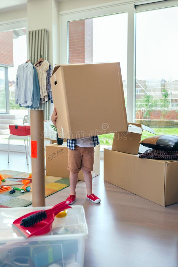 Boy carrying very large moving box royalty free stock photos