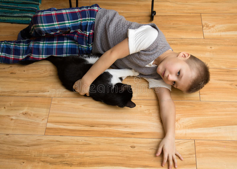 Little boy with a cat on the floor stock image