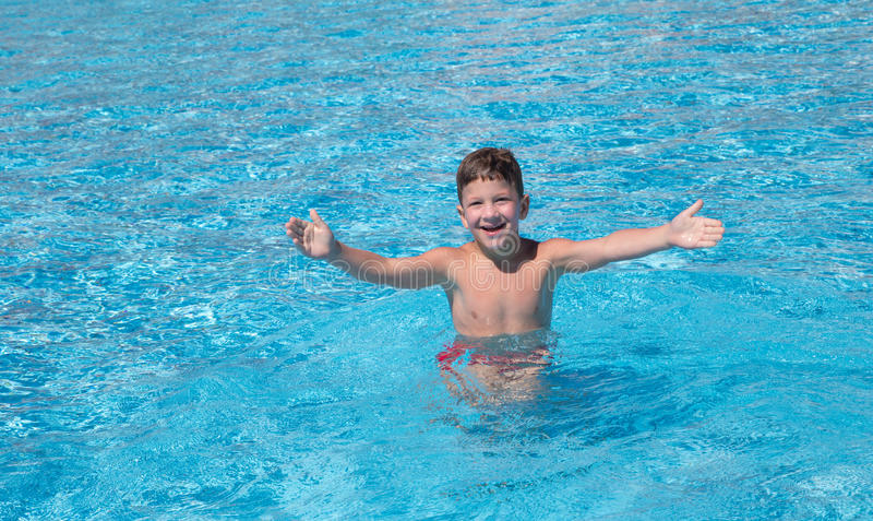 Little boy catching the ball in the pool stock image