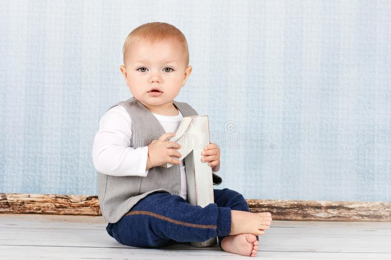 Little boy celebrates first birtday. Studio portrait of cute toddler holding wooden number one royalty free stock photos