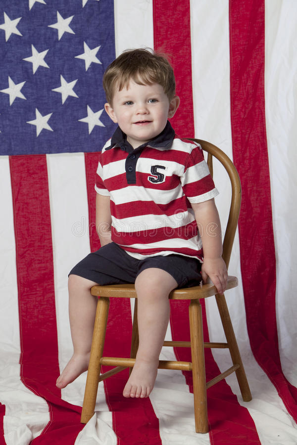 Little boy on chair with flag royalty free stock images