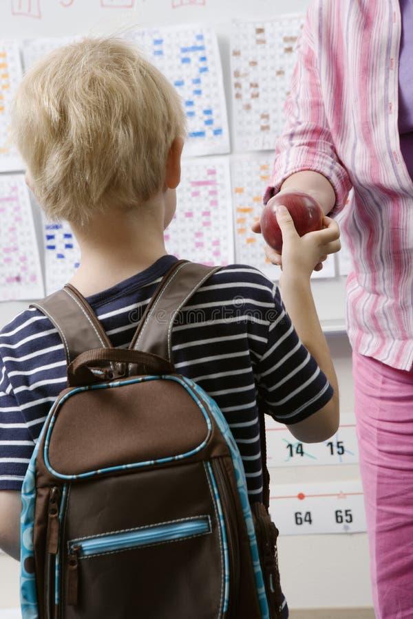 Little Boy che passa insegnante An Apple immagini stock libere da diritti