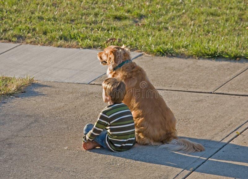 Little Boy che si siede con il suo cane fotografie stock libere da diritti