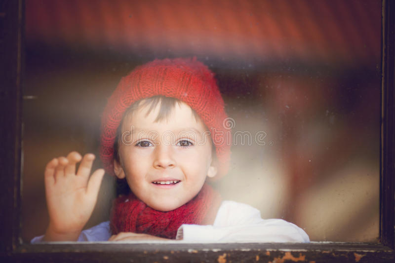 Little boy, child behind the window, wearing hat and scarf stock image