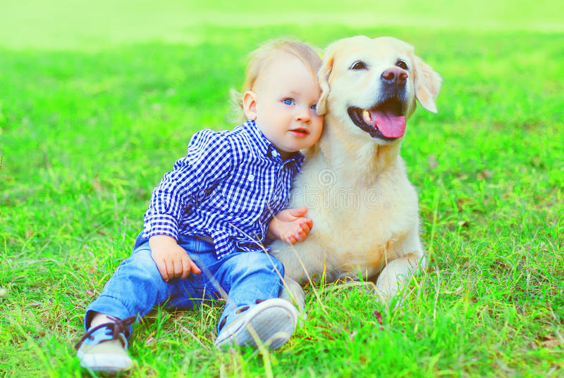 Little boy child and Golden Retriever dog is sitting together on the grass on summer royalty free stock photo