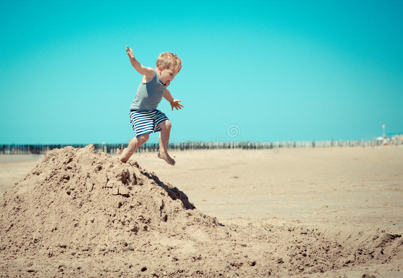 Little boy child jumps from a mountain on the beach royalty free stock image
