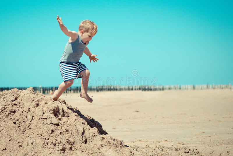 Little boy child jumps from a mountain on the beach stock images